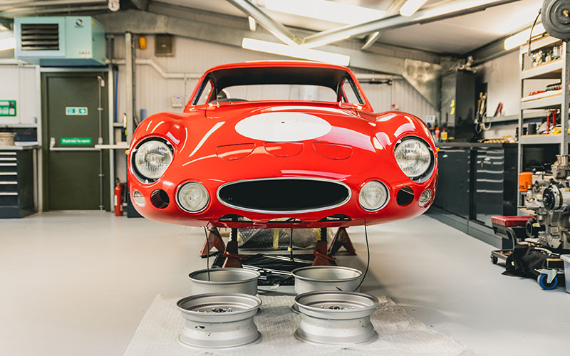 The shiny red shell of a classic car in a workshop, vintage car restoration finance options in action.